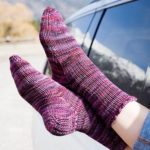 Purple toe-up socks with heel flap, shown out of car window