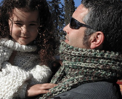 Man with chunky mistake-rib scarf holding daughter