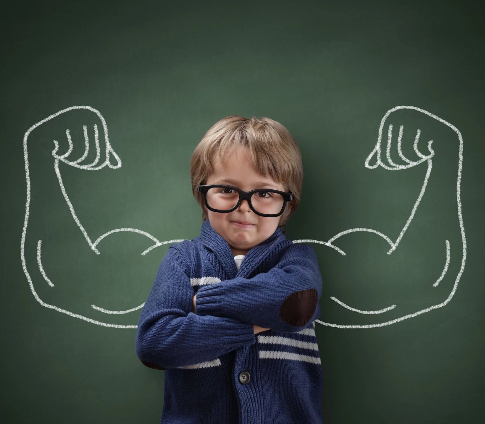 Child with strong arms drawn on chalkboard behind him