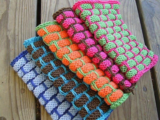 Stack of 4 brightly colored mosaic slip-stitch dishcloths in a 6-row brick pattern