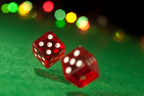 Red Dice Rolling on a Green Background