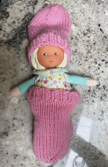 Doll wearing pink socks as sleeping bag and slouchy hat - KnitFreedom student Leila S.