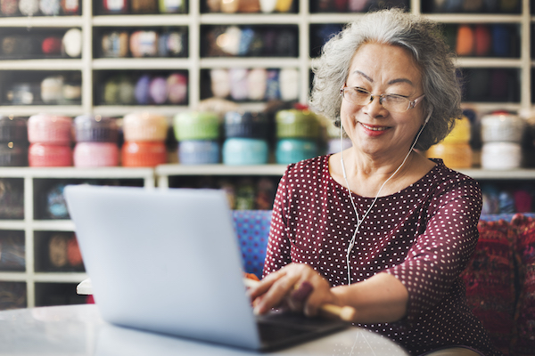 Woman in Yarn Store Looking Up Videos on Computer