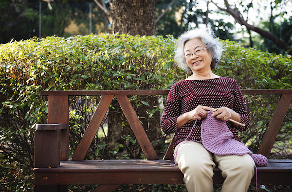 Woman knitting on park bench