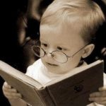 baby with glasses reading a book