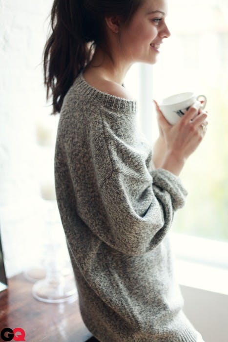 thin woman wearing sweater and holding a tea cup