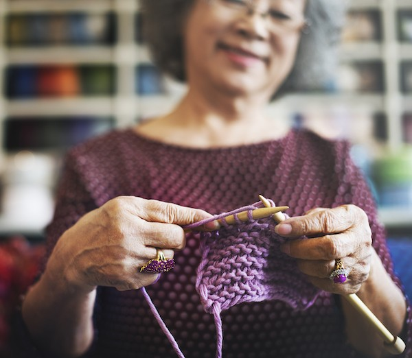 Woman proudly holding her knitting V1 sm